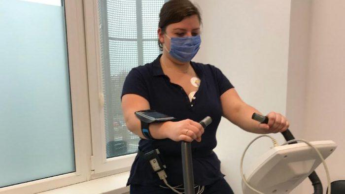 Zdjęcie: kobieta ubrana na czarno, w maseczce, ćwiczy na rowerze treningowym, u pasa ma urządzenie monitorujące.