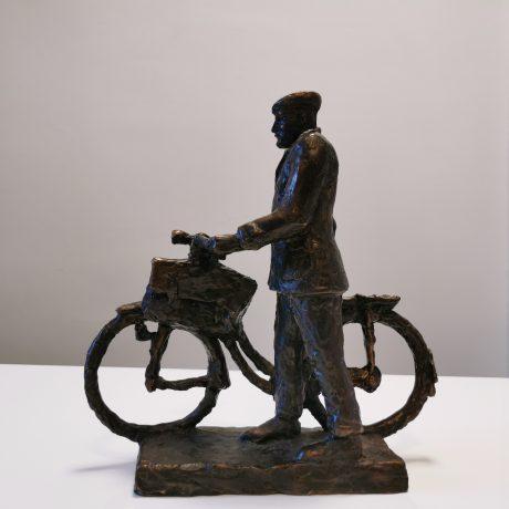 """Zdjęcie przedstawia statuetkę nagrody """"Senioribus optime meritis"""" - rzeźbę starszego mężczyzny z rowerem."""