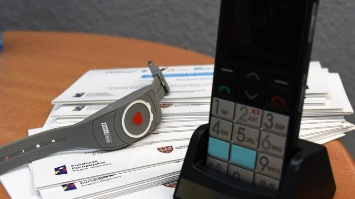 Telefon i opaska z pulsoksymetrem na stoliku