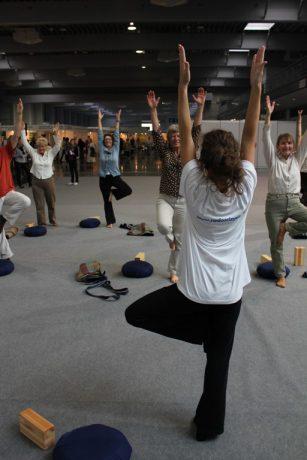 Na zdjęciu zajęcia jogo dla seniorów. Seniorki odwzorowują pozycje jogi, które prezentuje nauczycielka. Każda z uczestniczek ma przy sobie pomoce - drewniane klocki, poduszki i paski.