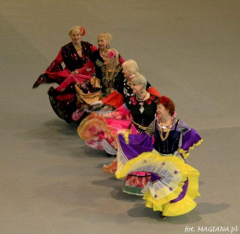 Na zdjęciu seniorki tańczą w kolorowych strojach. Niektóre maja kwiaty wplecione we włosy.