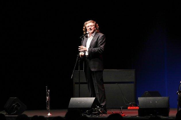 Na zdjęciu Zbigniew Wodecki podczas koncertu. Artysta śpiewa, ma na sobie elegancki garnitur, przed nie, przy krawędzi sceny stoi trąbka.