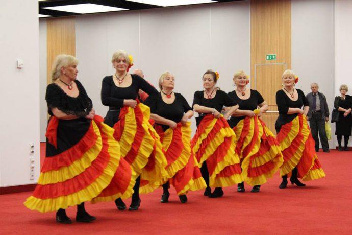 Seniorki tańczą flamenco w kolorowych strojach.