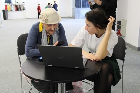 Na zdjęciu wolontariuszka Centrum Inicjatyw Senioralnych udziela konsultacji cyfrowych seniorce. Kobiety siedzą przy stoliku i korzystają z laptopa.