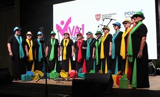 Występ Chóru Kameralnego Poznańskie Senioritki. Chórzystki mają na sobie czarne suknie, kolorowe chusty i kapelusze.