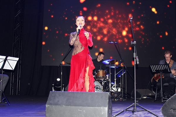 Zdjęcie wykonane w trakcie koncertu Grażyny Brodzińskiej. Artystka śpiewa na scenie, ma na sobie czerwoną sukienkę, w tle - towarzyszący jej zespół i wizualizacje wyświetlane na telebimie.