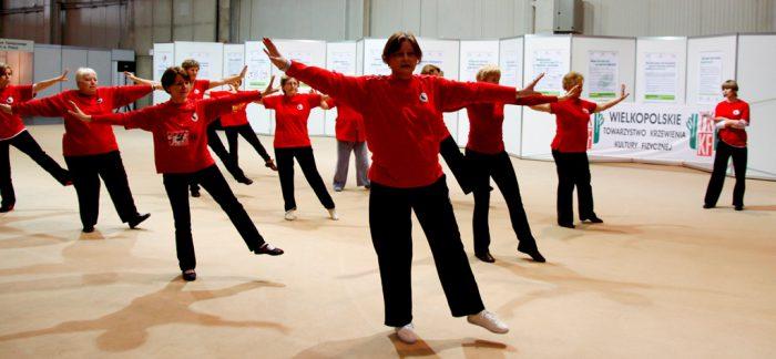 Na zdjęciu pokaz tai chi. Seniorki ubrane w czerwone koszulki i czarne spodnie wykonują sekwencję ćwiczeń.