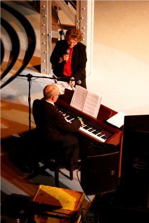 Zdjęcie podczas koncertu Ireny Santor. Artystka stoi przy pianinie i śpiewa. Na instrumencie gra muzyk z jej zespołu.