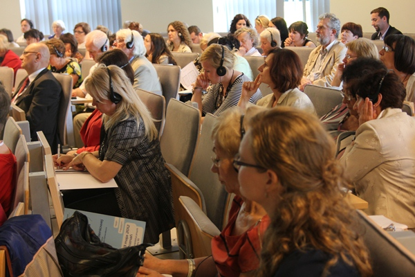 Na zdjęciu sala konferencyjna wypełniona po brzegi. Niektórzy uczestnicy maja na sobie słuchawki, niektórzy notują.