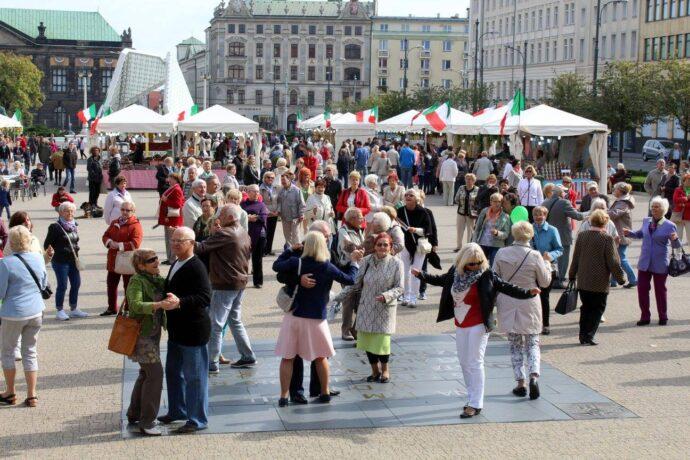 Na zdjęciu seniorzy i seniorki tańczą na placu Wolności.
