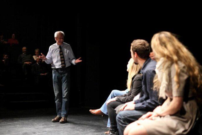 Zdjęcie podczas szkolenia ze storytellingu - aktor Aleksander Machalica stoi na przeciwko uczestników, gestykuluje.