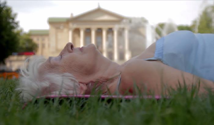 Na zdjęciu seniorka leży na trawie. Ma zamknięte oczy. W tle widać bydynek poznańskiej opery.
