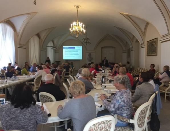 Forum Klubów Seniora w Sali Białej Urzędu Miasta Poznania. Uczestnicy siedzą przy stołach ustawionych w dwóch rzędach. Patrzą na przemawiającego mężczyznę.