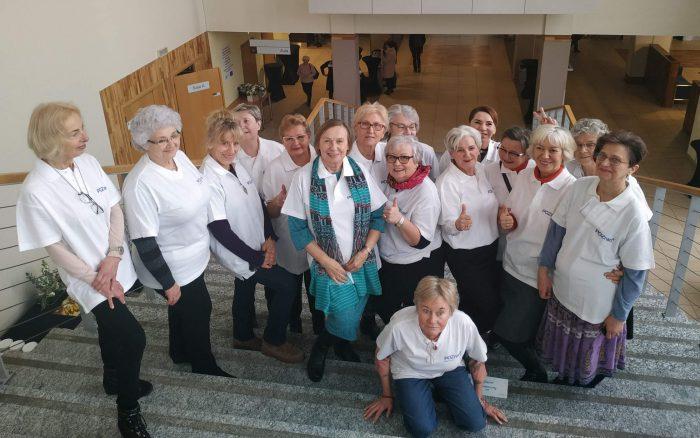 Wolontariuszki Centrum Inicjatyw Senioralnych stoją na schodach, wszystkie maja na sobie białe koszulki, uśmiechają się.
