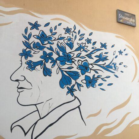 Zdjęcia murala senioralnego na ścianie kamienicy przy ul. Ślusarskiej. Na białym, o nierównych brzegach tle widać zarys profilu seniorki, zamiast rozwianych na wietrze włosów - niebieskie kwiaty.