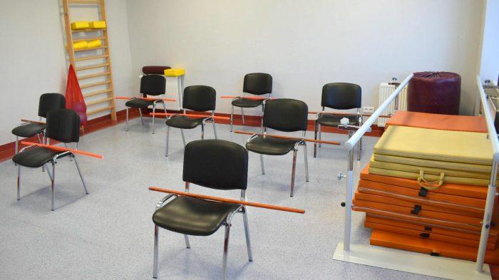 Zdjęcie sali do rehabilitacji: na środku krzesła z drążkami do ćwiczeń.