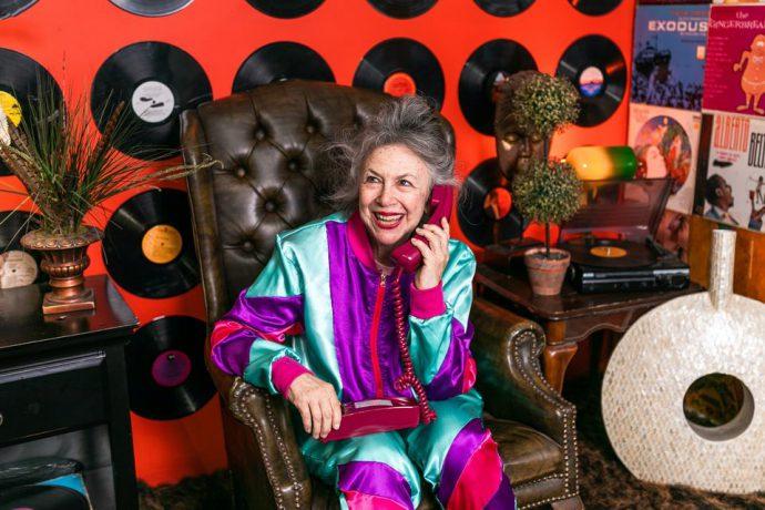 Na zdjęciu uśmiechnięta seniorka siedzi na pikowanym fotelu. Na kolanach trzyma telefon, a w reku, przy uchu słuchawkę. Ma na sobie kolorowy dres. W tle czerwona ściana wyklejona płytami winylowymi.