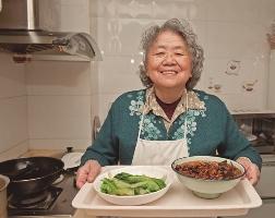Na zdjęciu starsza kobieta stoi w kuchni. Trzyma w ręku tacę, na której stoją dwa talerze. W jednym znajduje się danie o kolorze czerwonym, w drugim - zielone liście.