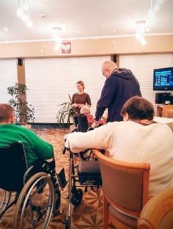 Na zdjęciu na pierwszym planie seniorzy na wózkach inwalidzkich podczas konsultacji dietetycznych w DPS. Na dalszym planie dietetyczka skierowana w stronę seniorów.