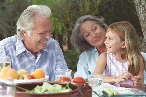 Na zdjęciu przy stole siedzi starsza kobieta, starszy mężczyzna oraz dziewczynka. Kobieta trzyma dziewczynka na kolanach, wszyscy się uśmiechają. Na stole stoją szklanki z wodą oraz miski z warzywami i owocami. W tle widać drzewa.