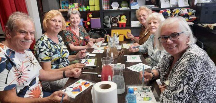 """Spotkanie w klubie seniora """"Niezły Młyn"""". Seniorki i seniorzy siedzą przy stole i wykonują prace plastyczne. Wszyscy się uśmiechają."""
