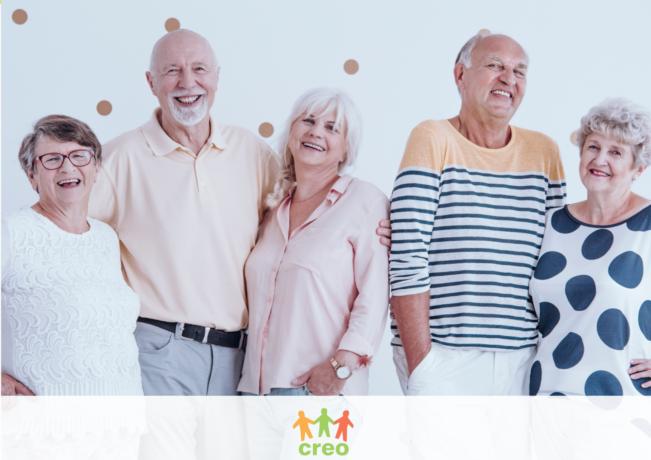 Na zdjęciu kilkoro seniorek i seniorów, wszyscy patrzą na wprost i się uśmiechają, w tle ściana z kropkami. Na dole logotyp Stowarzyszenia CREO.
