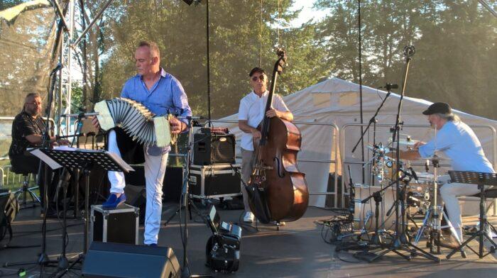 Na zdjęciu zespół muzyczny na scenie podczas Koncertu Sołackiego. Mężczyzna na pierwszym planie gra na organach i śpiewa, pozostali członkowie zespołu grają m.in. na kontrabasie i perkusji.