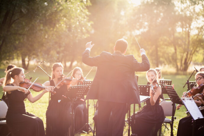 Na zdjęciu dyrygent dyryguje orkiestrą podczas koncertu, który odbywa się w plenerze. Za muzykami widać drzewa.