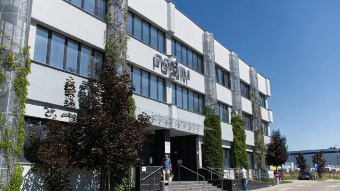 Na zdjęciu siedziba POSUM, w centrum główne wejście, biała fasada. Ze schodów schodzi starszy mężczyzna w maseczce.