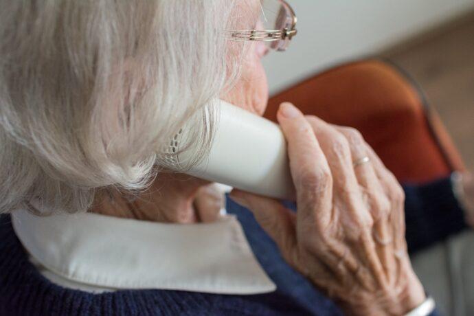 Na zdjęciu seniorka siedząca tyłem i rozmawiająca przez telefon.