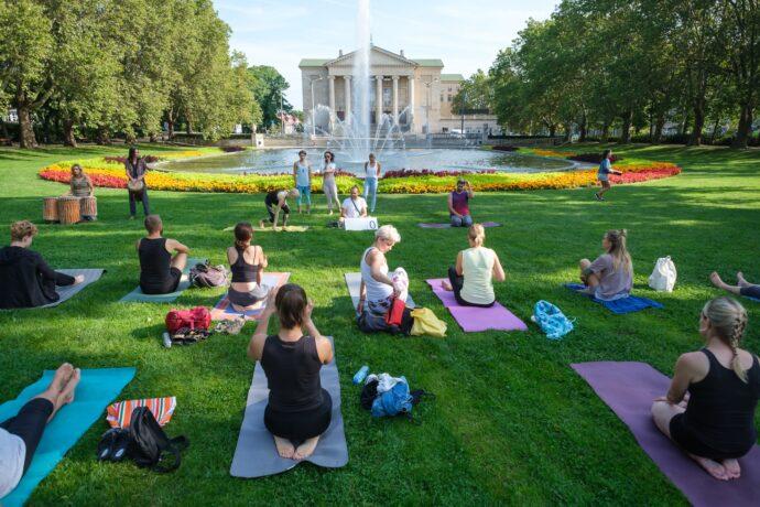 Na trawie przed fontanną trwa sesja jogi - jej uczestnicy wykonują asany na kolorowych matach.