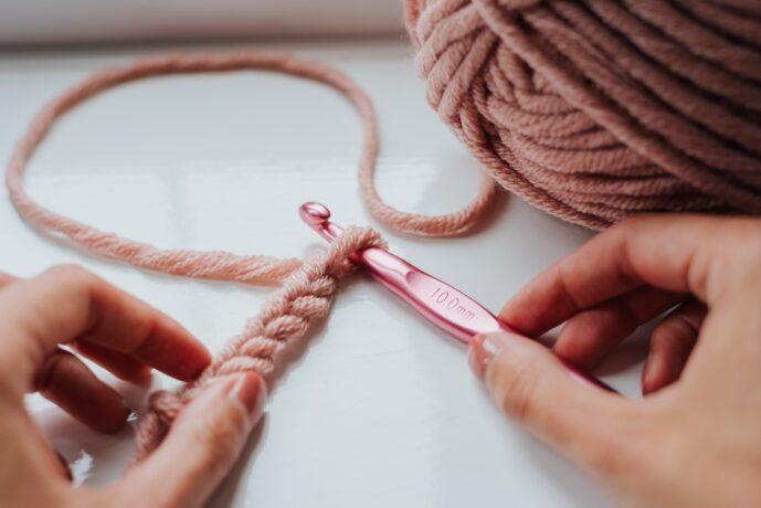 Na zdjęciu dłonie, jedna dłoń trzyma różowe szydełko, druga - włóczkę zaplecioną w warkocz, po prawej stromie kłębek różowej wełny.