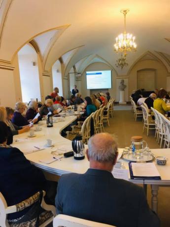 Zdjęcie wykonane podczas forum - w reprezentacyjnej sali w Urzędzie Miasta Poznania, przy półokrągłym, białym stole siedzą uczestniczki i uczestnicy spotkania. Na końcu stołu widać prowadzącego spotkanie.