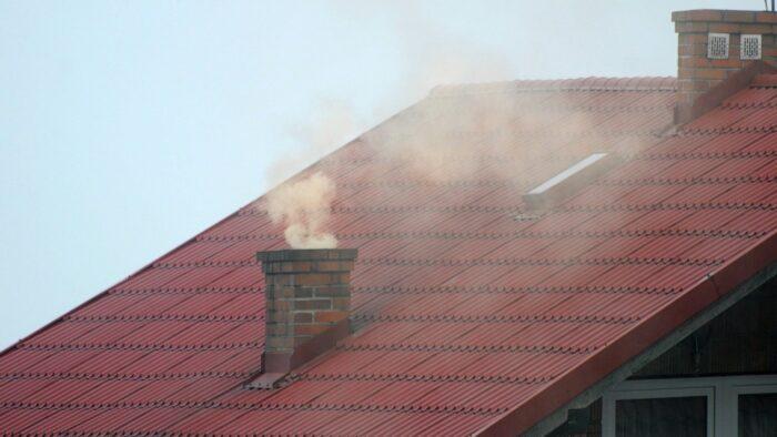 Zdjęcie przedstawia dach, na którym znajduje się komin. Z komina leci dym.