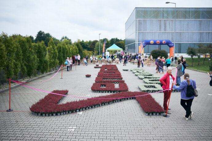 """Na zdjęciu napis """"Senioralny. Poznań"""" z wrzosów, widok z boku, od strony litery """"S"""". W tle uczestniczki i uczestnicy inauguracji."""