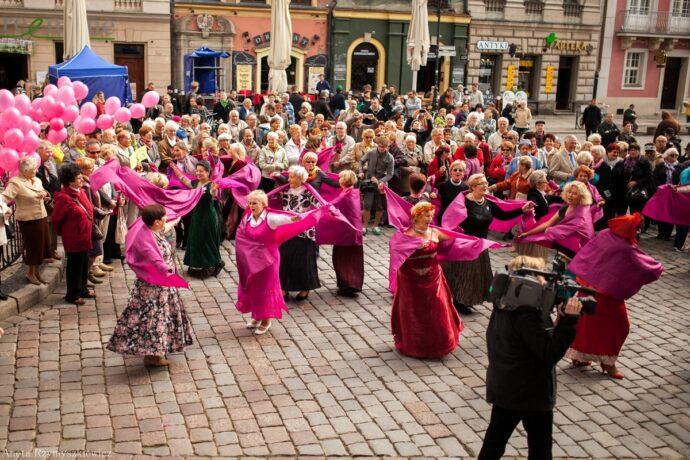 Na zdjęciu seniorki w różowych strojach tańczą na płycie Starego Rynku. W tle publiczność, różowe balony oraz kolorowe kamienice.