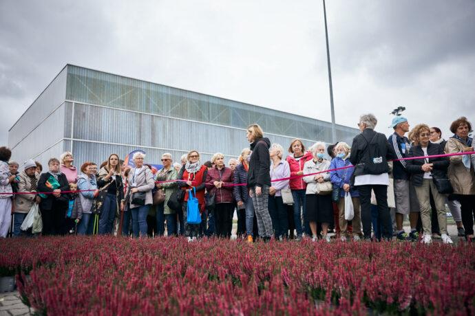 """Na zdjęciu seniorki seniorzy stoją przed wrzosowym napisem """"Senioralni. Poznań"""", przygotowują się do pamiątkowego zdjęcia. Na pierwszym planie wrzosy."""