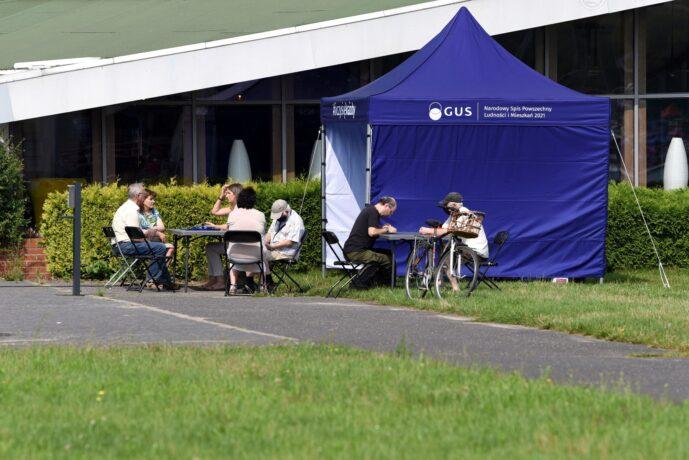 Na zdjęciu namiot, przy który ludzie siedzący przy stolikach uzyskują wsparcie podczas Narodowego Spisu Powszechnego.