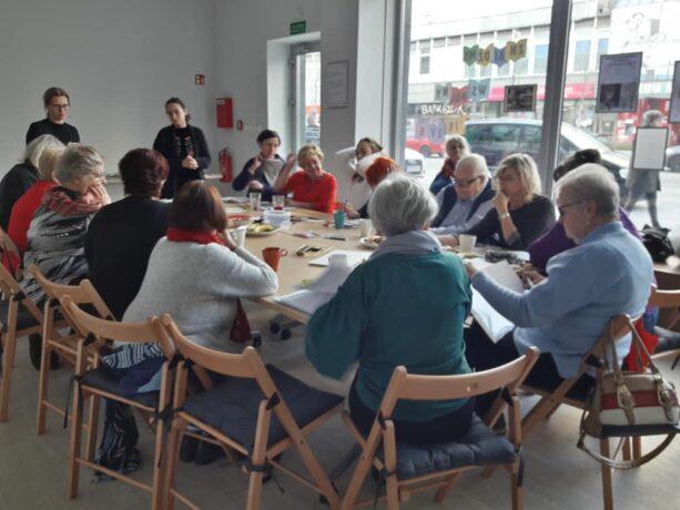 Warsztaty podczas pierwszej edycji Akademii Liderów i Liderek. Uczestnicy siedzą przy owalnym stole, u szczytu stołu dwie prowadzące warsztat.