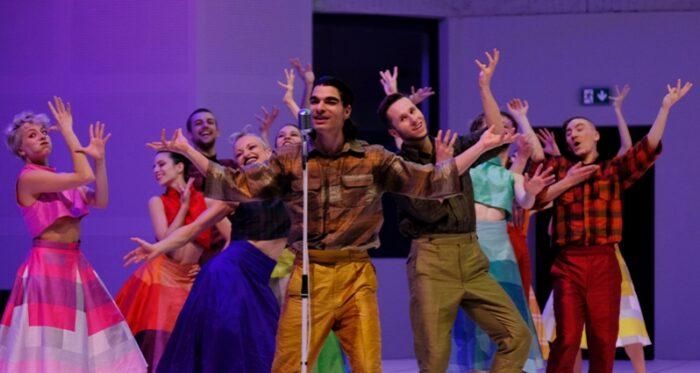 """Kadr ze spektaklu """"Kurka wodna albo urojenie"""" - tancerze w kolorowych strojach unoszą do góry ręce."""