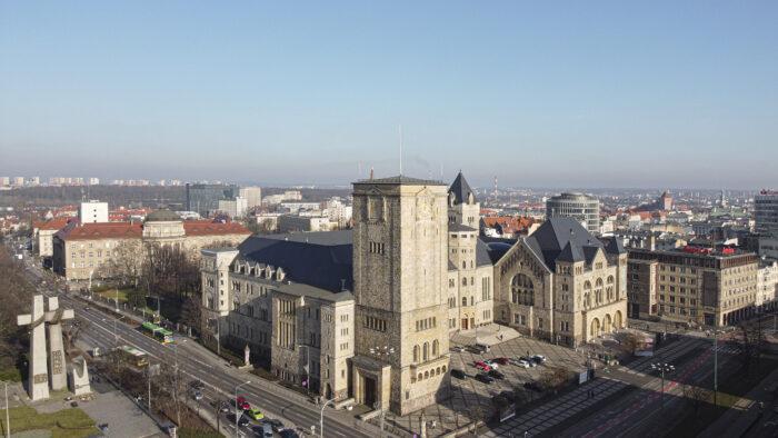 Zdjęcie Zamku z lotu ptaka - widać cały budynek, fotografia wykonana w słoneczny dzień, w tle widać panoramę miasta.